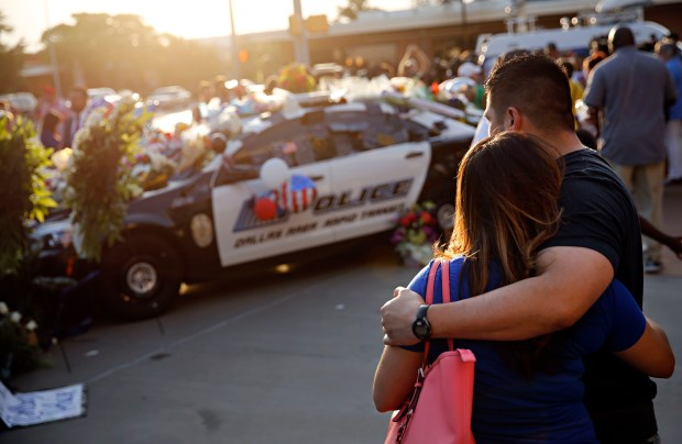 Passers-by stop at a vigil at Dallas police headquarters Friday, one day after 12 officers were ambushed by a sniper.