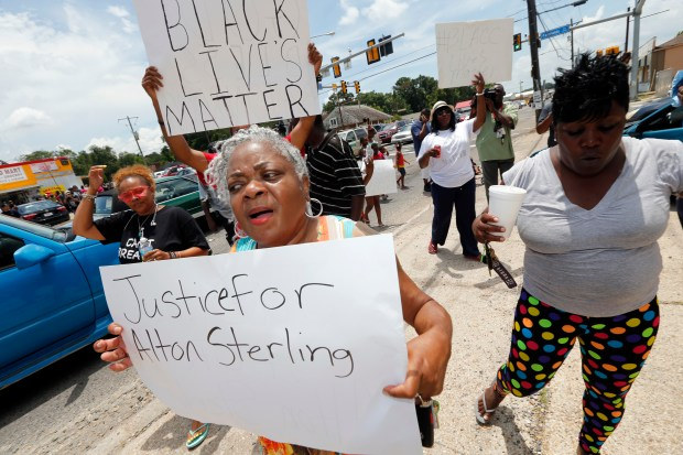 People march outside the convenience store, where Sterling was selling CDs. The Justice Department opened a civil rights investigation Wednesday into the videotaped shooting by police.
