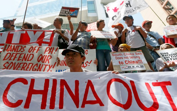 Protesters display their message during a rally outside of the Chinese Consulate hours before the Hague-based U.N. international arbitration tribunal announced its ruling on South China Sea Tuesday, July 12, 2016, in Makati city east of Manila, Philippines.