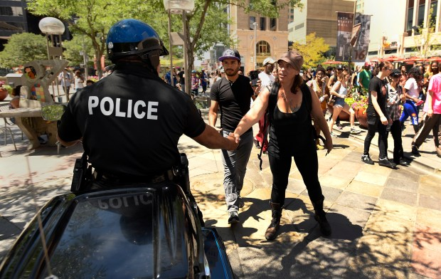 A protester shakes the hand of a Denver Police officer during a peaceful demonstration Monday on the 16th Street Mall.