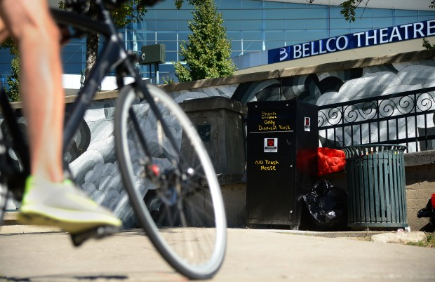People ride their bikes past the new used needle kiosk on Oct. 7, 2015, along the Cherry Creek Trail near Stout Street.