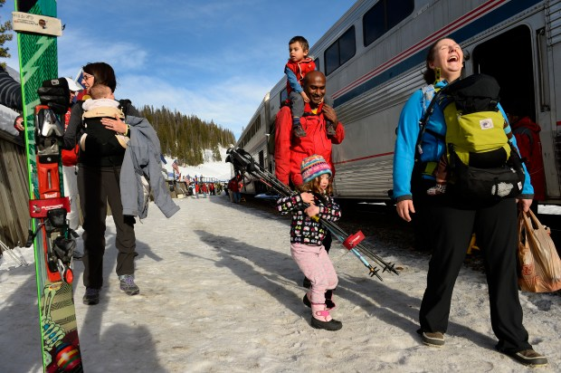 Val Hovland, right, laughs as young Emily Griffin, 4, says all the poles she tries to carry are too heavy as they head towards Winter Park after riding the Amtrak Winter Park Resort Ski Train at Winter Park, Colorado on March 15, 2014. Behind them are Hovland's husband Ram Sreerangam with young Kavi Hovland, 2 on his shoulders. For the first time since 2009 the Amtrak Winter Park Resort Ski Train made two trips from Denver's Union Station to Winter Park Ski area. The two trips sold out in a matter of hours and officials at Amtrak hope to work out a way to have the ski train come back on an annual basis. (Photo By Helen H. Richardson/The Denver Post)
