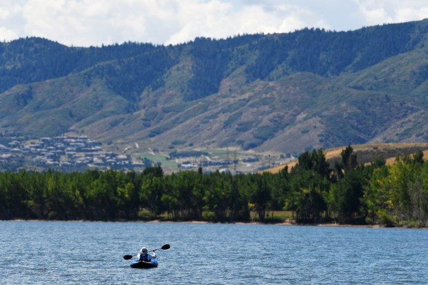 A kayaker makes their way along the west shore of the Chatfield Reservoir.