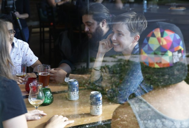 Diana Downard, 26, a Bernie Sanders supporter who now says she will vote for Hillary Clinton, has drinks with friends at a pub in Denver on July 6, 2016.