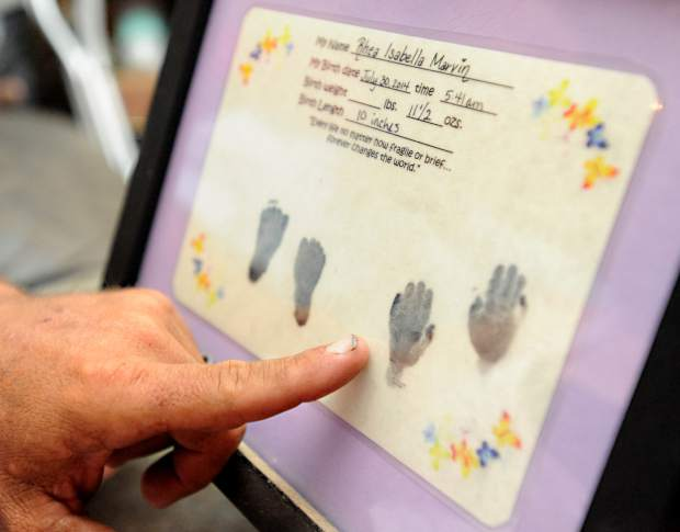 Tim Marvin points to the hand print of his daughter while at his home in Greeley. Sandy and Tim were among the many parents in Weld County to deal with the pain of stillborn and infant death.