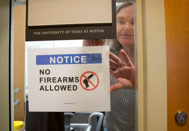University of Texas at Austin anthropology professor Pauline Strong posts a sign prohibiting guns at her office on the first day of the state's new campus-carry law on Aug. 1. The law, pushed by Gov. Greg Abbott and the Republican legislative majority, makes Texas one of a handful of states that guarantee the right to carry concealed handguns on campus.