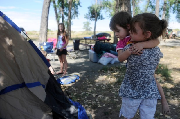 Gracee Mae Lucius, 9, holds her niece Zoey Smith, 2, to give her a better view of the tent. The pairs family was busy constructing the tent for them all to sleep in Saturday night at a Cherry Creek reservoir campsite Aug. 31, 2013.
