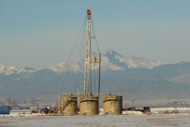 oil field worker places well pipe on a rig in Weld County.