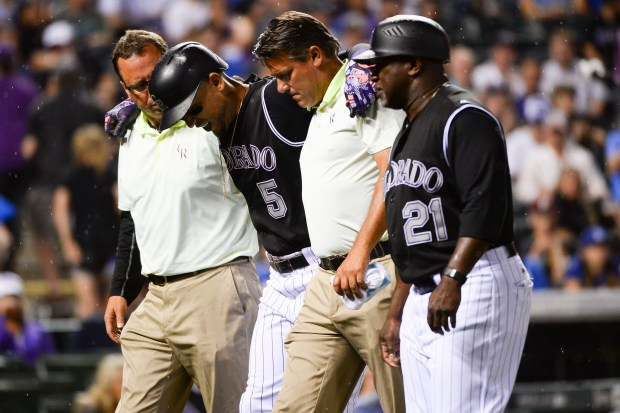 Colorado Rockies outfielder Carlos Gonzalez is helped off the field after rolling his ankle during an at-bat in the seventh inning of the game against the Los Angeles Dodgers at Coors Field on Aug. 3, 2016.