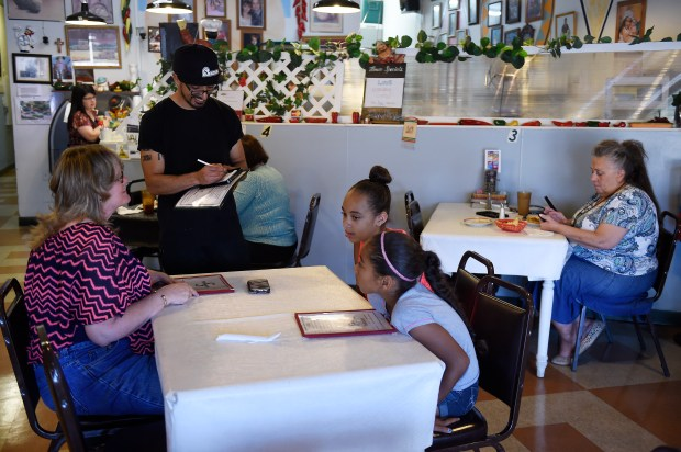 Earrol Perez takes a customers order at Senor Miguels in Aurora, Colorado on July 27, 2016. Six months ago, Aurora approved the creation of a new 6.8-acre urban renewal area at the northeast corner of South Sable Street and East Alameda Avenue for the redevelopment of the existing bank and shopping center into a quality transit-oriented development. The center, like many in Aurora, has been in decline, but this particular one is planned to be at the city center stop of the R-Line. (Photo by Seth McConnell/The Denver Post)