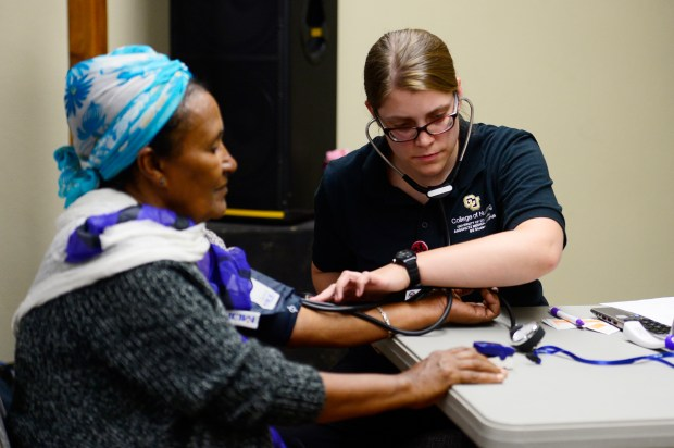 Michelle Loose, a University of Denver accelerated nursing student, checks the blood pressure for patient Elife Bzuneh, during a medical clinic night at the DAWN clinic on August 9, 2016, in Aurora, Colorado. DAWN is a student-run clinic established to serve uninsured patients in Aurora at no cost. It opened in March 2015. (Photo by Anya Semenoff/The Denver Post)
