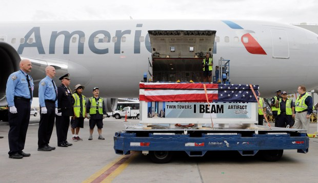 U.S. Customs and Border Protection agents and members of Miami-Dade Fire Rescue Department honor the arrival of a 2,000-pound World Trade Center steel beam enclosed in a case draped with the U.S. flag at Miami International Airport in Miami Aug. 13, 2015.