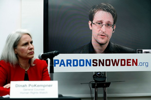 Dinah PoKempner, general council for Human Rights Watch, listens as Edward Snowden speaks on a television screen via video link from Moscow during a Sept. 14 news conference to call upon President Obama to pardon Snowden before he leaves office.