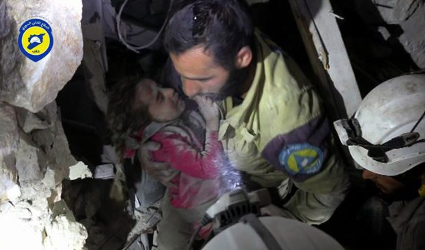 This Sept. 28 photo shows a Civil Defense worker carrying survived child Ghazal Akhtarini from under the rubble after airstrikes hit the al-Shaar neighborhood in Aleppo, Syria.