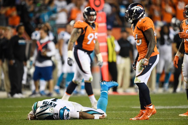 Cam Newton (1) of the Carolina Panthers lies on the turf after getting hit hard by Darian Stewart (26) of the Denver Broncos and Shaquil Barrett (48) during the fourth quarter of the Broncos' 21-20 win. The Denver Broncos hosted the Carolina Panthers on Thursday, September 8, 2016. John Leyba, The Denver Post