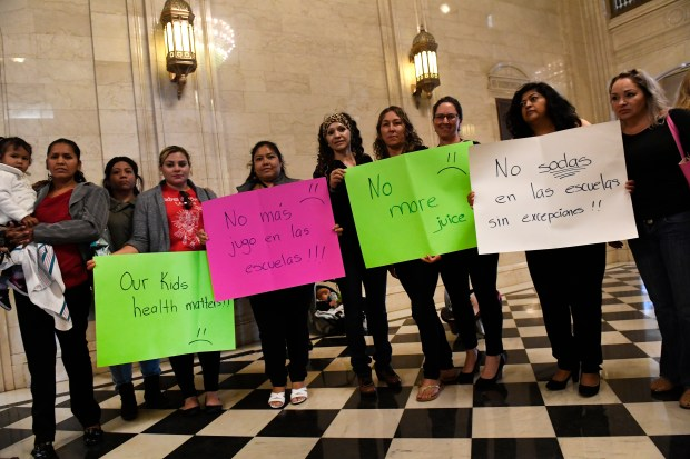 Members of the group Westwood Unidos hold signs before a State Board of Education hearing last Wednesday regarding whether to end Colorado's seven-year ban on diet sodas in high schools. Despite public comment against lifting the ban, the board voted 4-3 to end it.