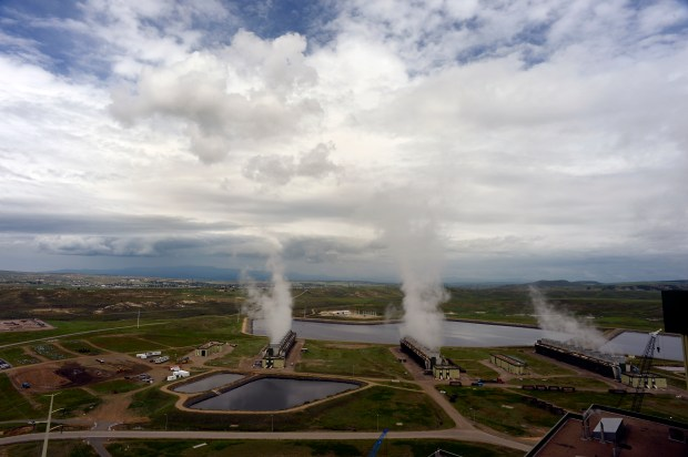 Three large cooling facilities evaporate off excess steam from water cycling through the Craig Station Power Plant in Craig, Colorado on June 10, 2015.