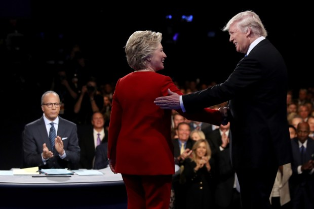 Hillary Clinton and Donald Trump shake hands as moderator Lester Holt looks on before Monday's presidential debate at Hofstra University in Hempstead, N.Y. Afterward, fact checkers found fault with all three.
