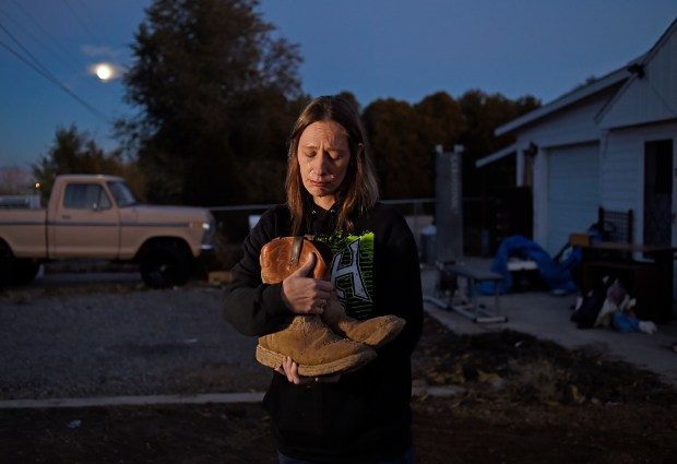 Sharon Hill holds her late husband's muddy boots outside her home in Grand Junction. Shane Hill was one of at least 51 oil and gas workers who were killed in Colorado since 2003.