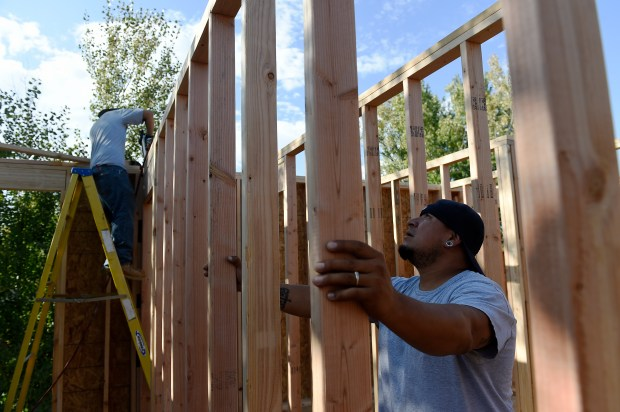 Louis Ortiz Jr holds a wall in place as Casey Lambert nails it in place as they work on a second story addition to the Ortiz's home on Mildred Dr in Northglenn on Sept. 22, 2016.