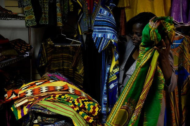 Vida Amoah folds dresses in the Africa Fashion and Arts store at Afrikmall in Aurora, Colorado on September 6, 2016. The Afrikmall in Aurora has finally opened a portion of the space. The dual level space has single tenants on the bottom floor and an unused upper level that the Aurora Cultural Arts District is possibly going to buy as studio space for resident artists.
