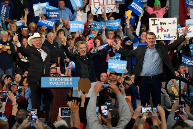 Hillary Clinton, center, along with former Secretary of the Interior Ken Salazar, left, and Colorado U.S. Senator center, Michael Bennet at the conclusion of the Colorado Democratic Party Rally at the Palace of Agriculture on the Colorado State Fairgrounds October 12, 2016.