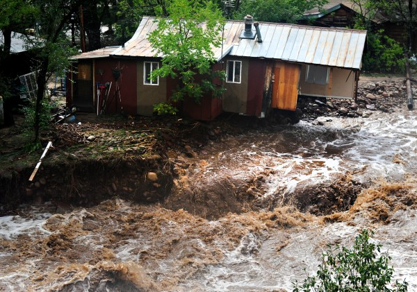 This file photo shows flood waters raging along the South St. Vrain River in Lyons, Sept. 13, 2013.