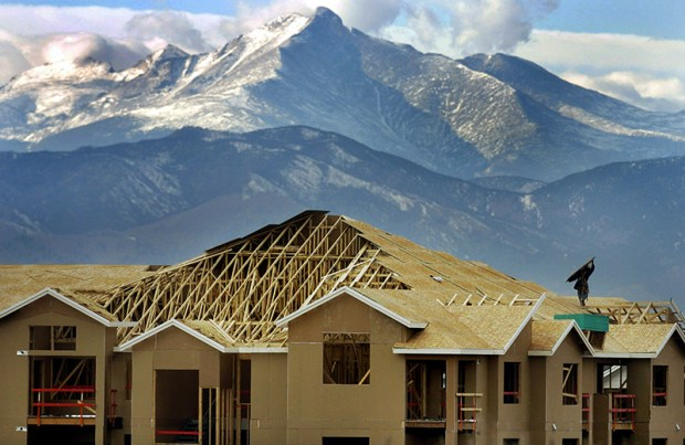 Longs Peak looms behind a condomium being built in Erie in 2004. Building the housing needed for Colorado's growing population has converted millions of acres of wildlife habitat, agricultural lands and open spaces.