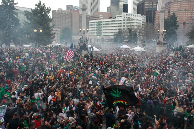 In this April 20, 2013, file photo, members of a crowd numbering tens of thousands smoke marijuana and listen to live music at the Denver 420 pro-marijuana rally at Civic Center Park in Denver.