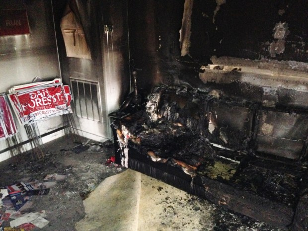 A burned couch is shown next to warped campaign signs at the Orange County Republican Headquarters