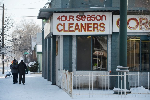 Folks walk past Four Seasons Cleaners Thursday morning, February 06, 2014 along Bruce Randolph Ave near York St.