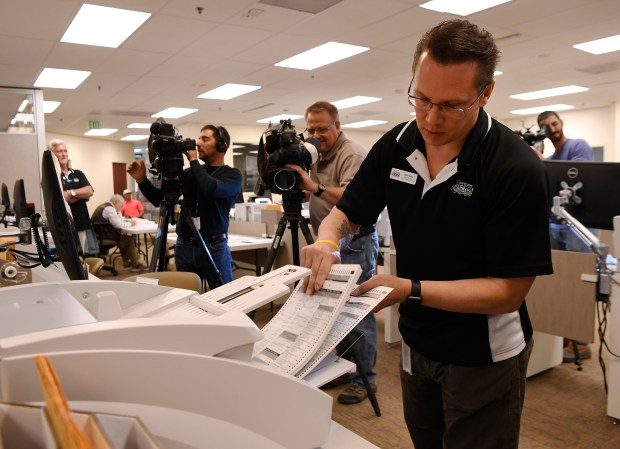 Denver Elections senior GIS analyst Steve Sharp loads test ballots into a scanner during a test of the ballot system in the counting room at the Denver Elections headquarters October 13, 2016.