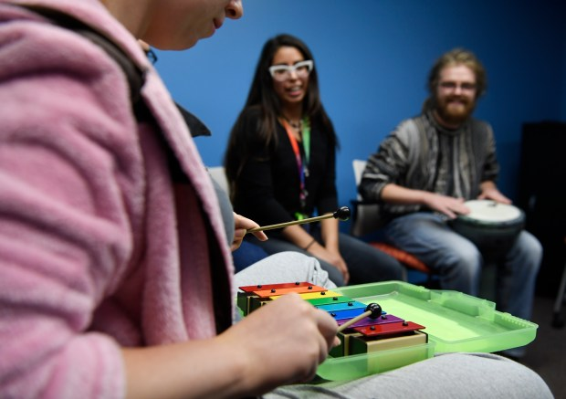 A Mental Health Center of Denver participant, left, plays a tune in a drum circle at the Emerson Street for Teens and Young Adults October 25, 2016. MHCD administrative assistant Amorette Quintanilla, center, and volunteer Brennan Forrester, right, listen.