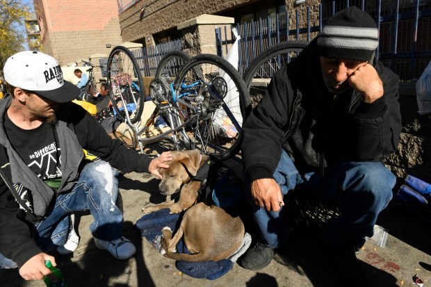 James Anderson, left, pets his dog Honey, while he sits on the sidewalk with his friend John Crespin, right, near the Denver Rescue Mission along Park Ave West on October 26, 2016 in Denver, Colorado. After the city performed sweeps to clean up the streets and move the homeless people, those folks have come back to the area seemingly with nowhere else to go.