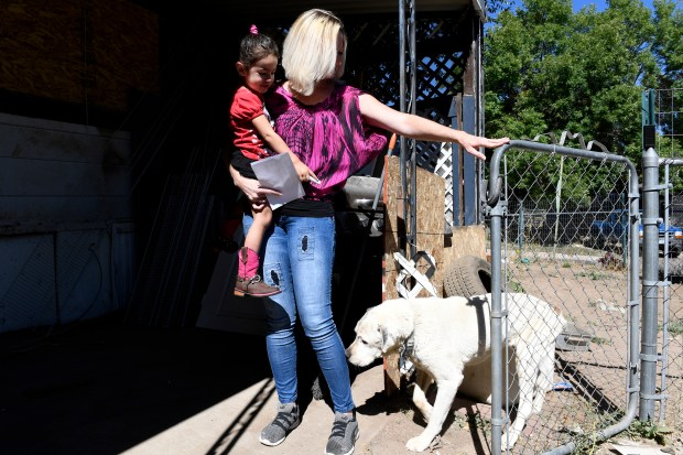 Drina Carbajal, holding her daughter Gabriela, 2, lets her dog Spot out of the front yard