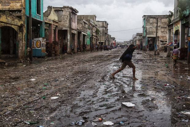 In this photo released by UNICEF, a woman crosses the street on a flood effected road as hurricane Matthew passes over on October 4, 2016 Port au Prince. Weakened but still dangerous, Hurricane Matthew churned toward the Bahamas Wednesday en route to an already jittery Florida after killing at least nine people in the Caribbean in a maelstrom of wind, mud and water. Logan Abassi, AFP/Getty Images