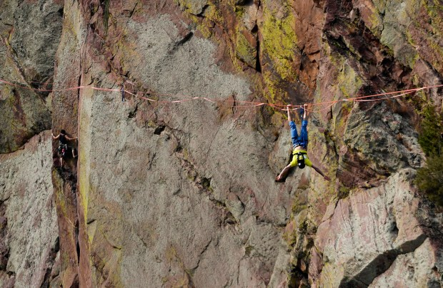 Taylor VanAllen, 24, right, does tricks on his high line, high above a rock climber, to the left, after making the FA, or First Across, on a high-line from the Wind Tower rock formation to the Bastille rock formation 450 feet off the ground and just shy of 600 feet across in Eldorado Canyon State Park on October 15, 2016 in Golden, Colorado. VanAllen, an athlete with Slackline Industries, recreated the historic Ivy Baldwin high line crossing of Eldorado Canyon in a benefit for trail building at the state park.  VanAllen crossed from the exact location as the legendary Baldwin.  Baldwin, who was a high wire performer, did the crossing on a high wire over 80 times in his lifetime. The last time he made the 600 foot walk was on his 82nd birthday in 1948. VanAllen's walk was the first ever by a High Line walker on a slack line.