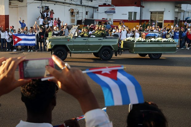A military truck pulls a trailer with the flag-draped chest that holds the remains of former Cuban President Fidel Castro as thousands of Cubans line the famous Malecon seaside boulevard to pay their respects Thursday in Havana.