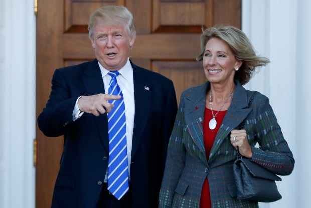 President-elect Donald Trump and Betsy DeVos pose for photographs on Nov. 19 at Trump National Golf Club Bedminster clubhouse in Bedminster, N.J. Trump has chosen DeVos, a charter school advocate, as his education secretary in his administration.
