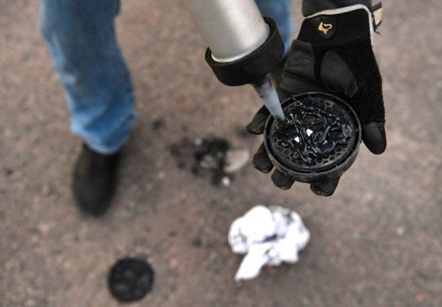 Parkifi Installation specialist Dathan O'Boyle puts adhesive material on a Parkifi sensors before placing it into a parking spot at a surface parking lot at at 1811 Lincoln street on November 2, 2016 in Denver, Colorado. Parkifi is rolling out a parking App that will help users find open parking spots around the metro area. This one mixes hardware, such as the sensors placed in the middle of each parking spot, with software to help guide you to open spots and let you know which ones are taken using an App on your phone.