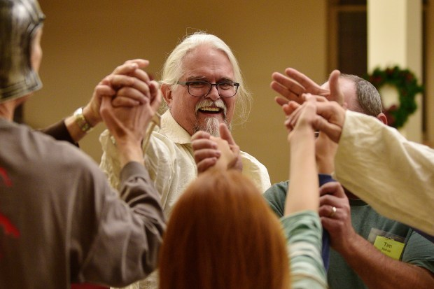 Cast member Cole Keirsey (center) holds hands with fellow cast members during an evening rehearsal for the Rocky Mountain Revels at First Congregational Church in Boulder.