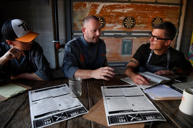 Punch Bowl Social regional executive chef Matt Selby, left, and Culinary Operations Director Christopher Cina, center, talk with celebrity chef and PBS culinary partner Hugh Acheson discuss menu changes and upgrades at the Denver location November 1, 2016.