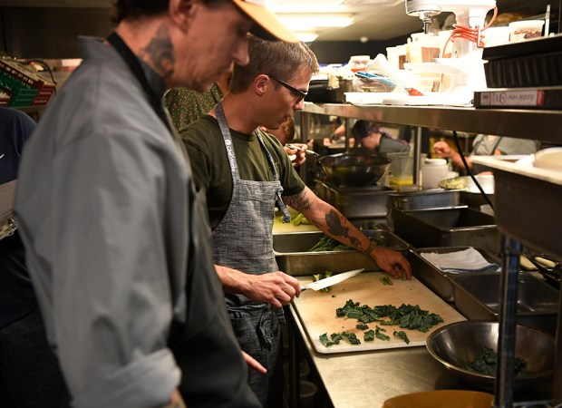 Punch Bowl Social culinary partner and celebrity chef Hugh Acheson, right, works with PBS regional executive chef Matt Selby on re-working the Dino kale caesar salad in the kitchen of the Denver restaurant November 1, 2016.
