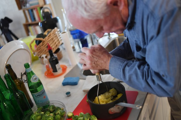 Bill St. John prepares side dishes for Thanksgiving at his home in Denver, November 3, 2016.