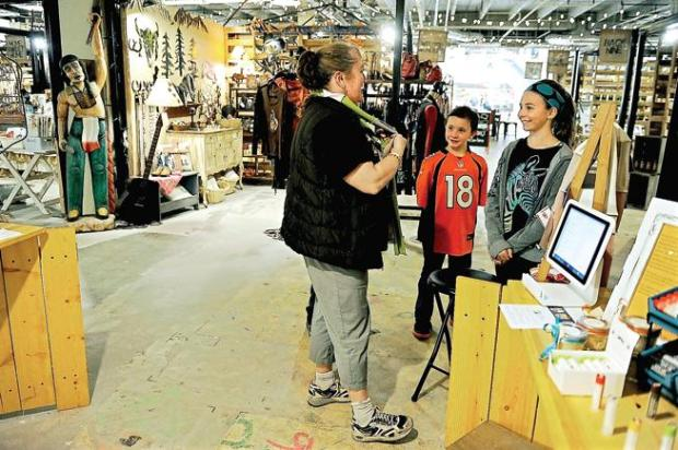 Anjie Julseth-Crosby tries on a scarf made by Aubrianna Roberts, 11, right, as Jack Bonneau, 10, watches at the Jack's Stands Marketplace in the Southwest Plaza Mall Makers Marketplace in Littleton earlier this year.
