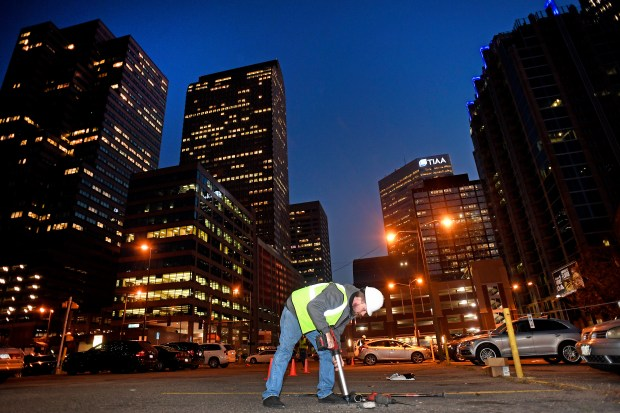 DENVER, COLORADO - OCTOBER 2: Parkifi Installation specialist Dathan O'Boyle punches out a hole in the asphalt to be able to place Parkifi sensors in parking spots at a surface parking lot at at 1811 Lincoln street on November 2, 2016 in Denver, Colorado. Parkifi is rolling out a parking App that will help users find open parking spots around the metro area. This one mixes hardware, such as the sensors placed in the middle of each parking spot, with software to help guide you to open spots and let you know which ones are taken using an App on your phone.  (Photo by Helen H. Richardson/The Denver Post)