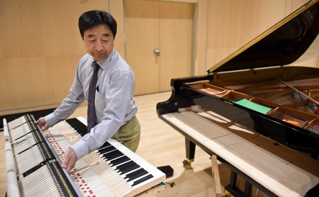 Master Piano Artisan Takanori Otake lifts the keyboard back into the Shigeru Kawai piano Wednesday at the Longmont Museum and Cultural Center.