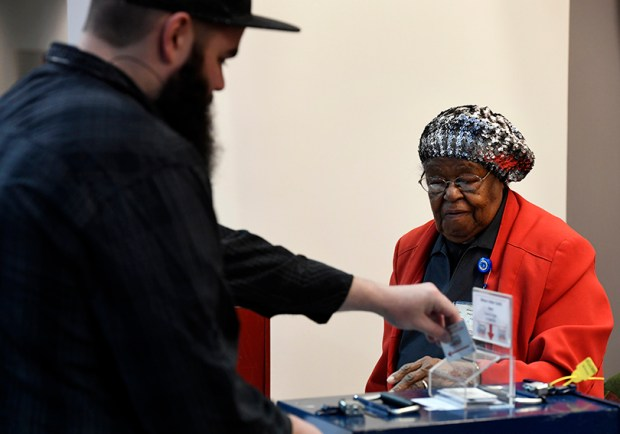 Longtime election judge Rev. Josephine Falls keeps a close eye on a voter at Denver Elections Division headquarters on Tuesday.