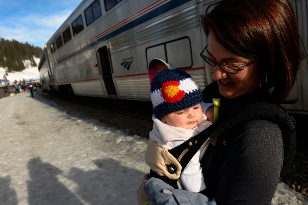 WINTER PARK, CO -- Skier Rachel holds baby Kerry as the two prepare to head towards Winter Park after riding the Amtrak Winter Park Resort Ski Train at Winter Park on March 15, 2014.