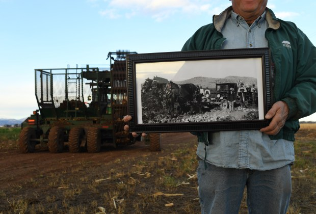 Richard Seaworth holds a photo of his father, and others, working at their sugar beet farm in1929